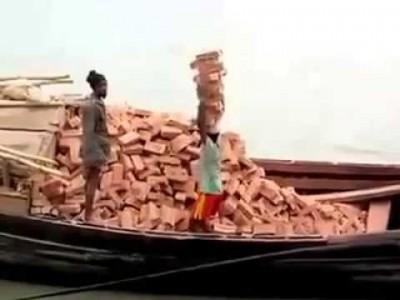 A woman stacks  unprocessed bricks
