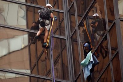Officers from the NYPD attempt to detain a man as he climbs the outside of Trump Tower. REUTERS/Lucas Jackson