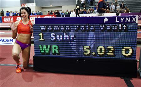 Jenn Suhr poses next to the score board after setting a new women's indoor pole vault world record at the USA Indoor Track and Field Championships in Albuquerque