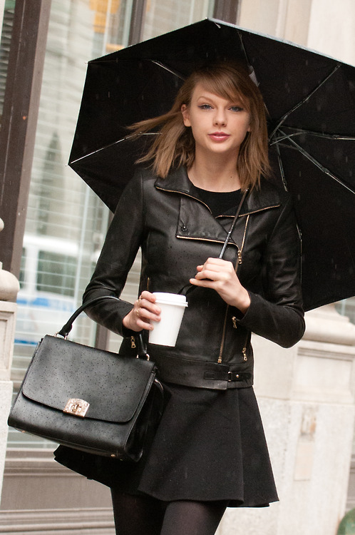 Taylor Swift in Black Leather Jacket with drink and umbrella on hand.
