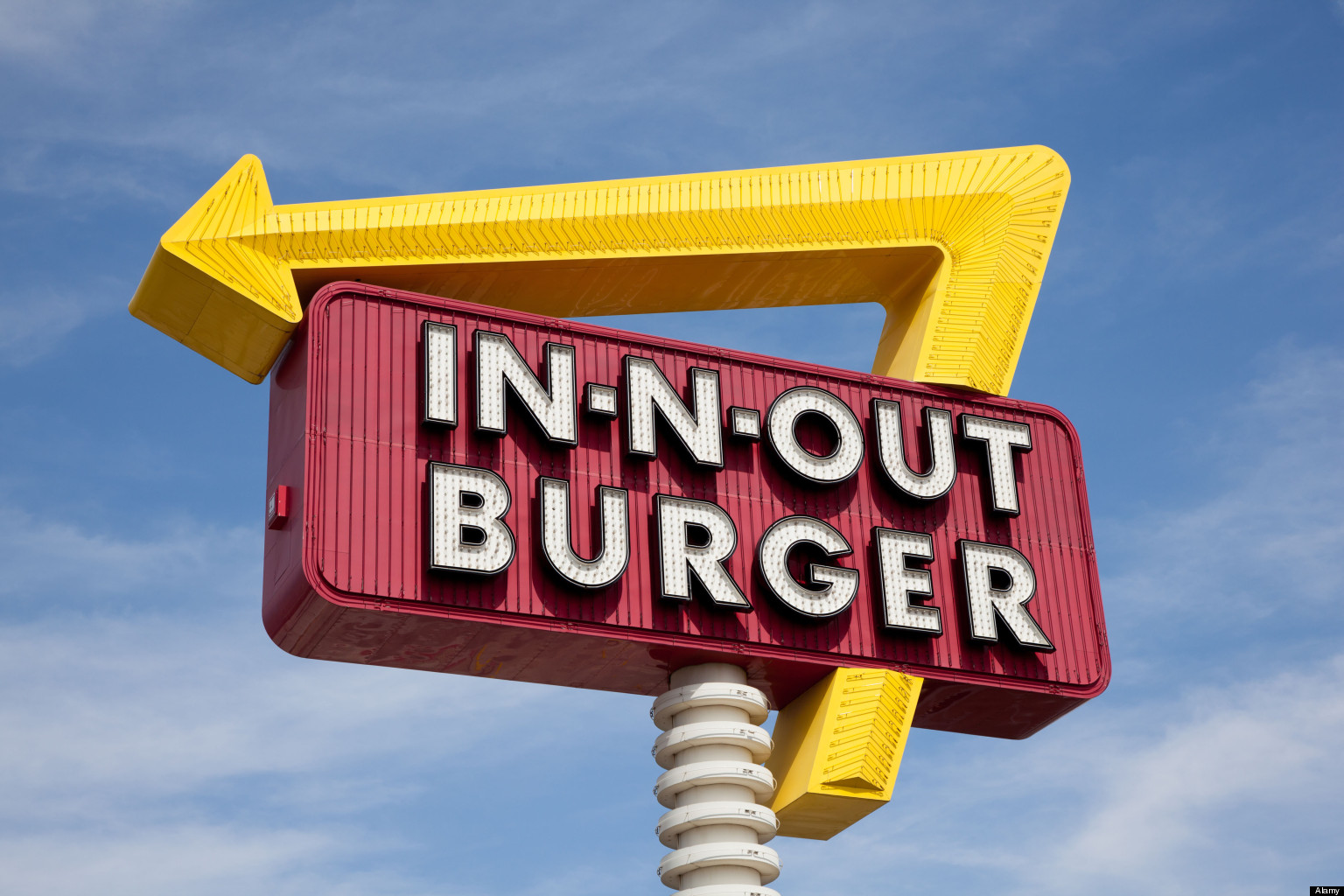 A classic IN-N-OUT BURGER sign in front of blue sky with yellow arrow