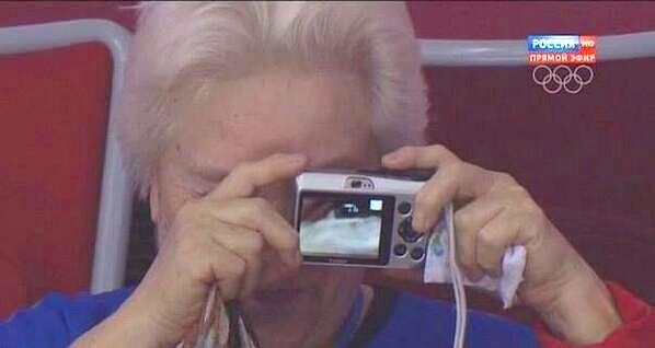 woman attempting to take a picture at a hockey game in Sochi